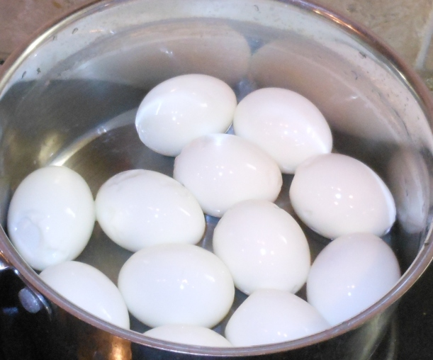 The eggs are boiled, peeled, and ready, so I add them to the meat mixture.
