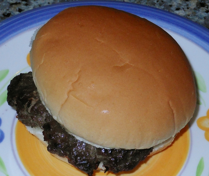 Cooked hamburger patties in a hamburger bun.