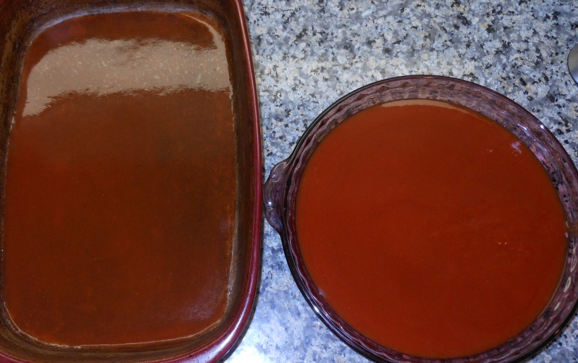 I prepped my 9x13 casserole dish by pouring a little enchilada sauce in the bottom of the pan, then I poured the remaining sauce into a pie tin.  I find it is the perfect size and shape for dipping the tortillas in the sauce.
